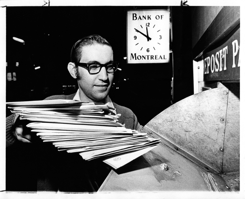 "A man in dress shit, pullover sweater and heavy, dark rimmed glasses places a stack of envelopes in a mail slot out side a bank. A large clock featuring the words""Bank of Montreal"" is visible in the background."