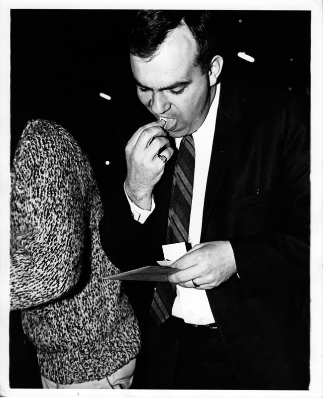 A man in a suit and tie licks a stamp for an envelope he is about to mail. A person is a heavy cable sweater is visible in the background.