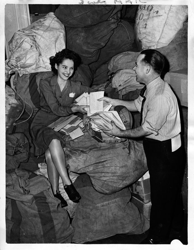 A young woman in a dress is seated on top of a heap of mail bags, posing with a man with a handfull of tax forms.