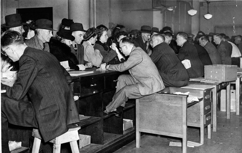 Eight men in suits are visible seated on high stools or re-purposed desks while dealing with large line ups of men and women submitting their tax forms in 1946.