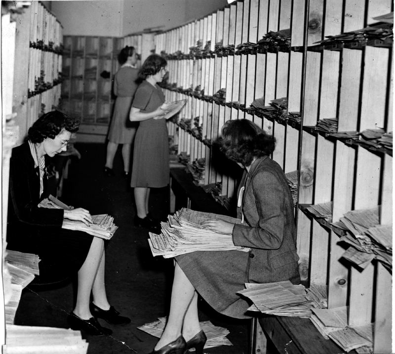 Fourwomen sit on benches or stand to file stacks of tax forms into large square slots lining a room.