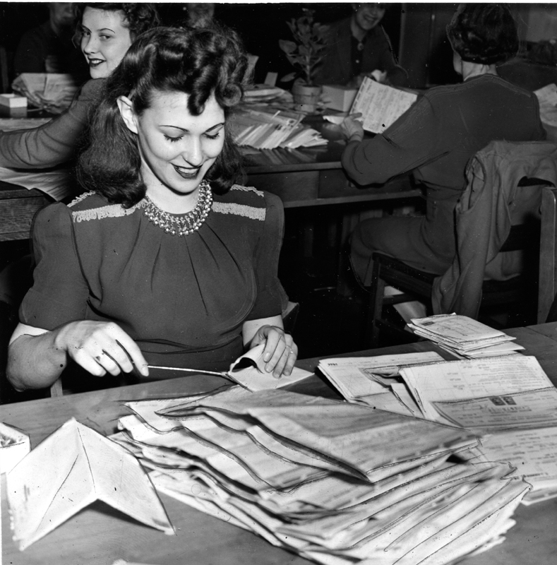A young woman in a dress opens mailed tax forms and piles them before her on a desk. Three women performing similar tasks are visible in the background.