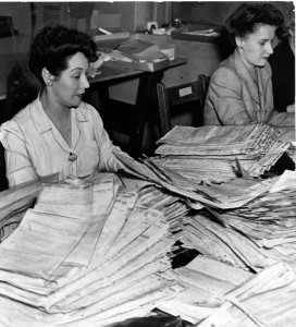 A woman in a light coloured blouse works at a deask piled high with income tax forms. A woman in a suit jacket is visible in the background.
