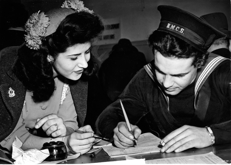 An unidentified H.M.C.S. sailor in uniform filing a tax return while a woman in a flowered hat looks on.