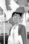Image of Clara Thomas with cap and academic robes on standing in front of a Canadian flag, 1986. Clara Thomas fonds, F0432, image no. ASC00510.
