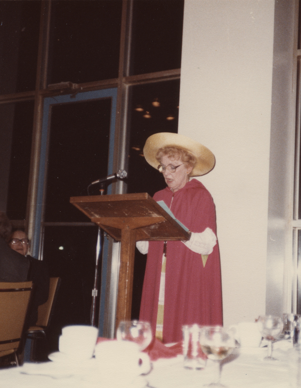Image of Clara Thomas wearing red academic robes with a wide brimmed hat speaking at a lectern, ca. 1984. Clara Thomas fonds, F0432, image no. ASC00511.