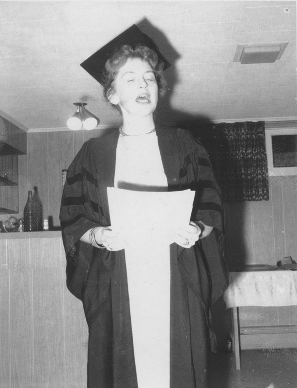 Image of Clara Thomas in graduation gown reading from a text, 1962. Clara Thomas fonds, F0432, image no. ASC00513.