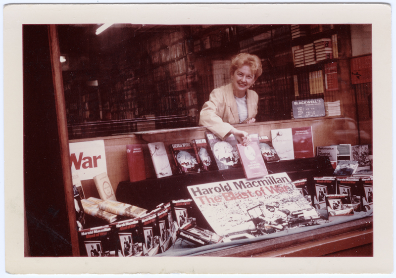 """Image of Clara Thomas leaning over the display window of Blackwell's Book Store in Oxford, England, holding a copy of her book above a display featuring Harold Macmillan's """"The Blast of War"""". Clara is smiling out to the photographer. 1967. Clara Thomas Archives & Special Collections, Clara Thomas fonds, F0432, image no. ASC07977."""