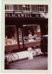 "Image of Clara Thomas leaning over the display window of Blackwell's Book Store in Oxford, England, holding a copy of her book above a display featuring Harold Macmillan's ""The Blast of War"". Clara is smiling out to the photographer, who is positioned from a distance, probably in the middle of the street, 1967. Clara Thomas Archives & Special Collections, Clara Thomas fonds, F0432, image no. ASC07978."