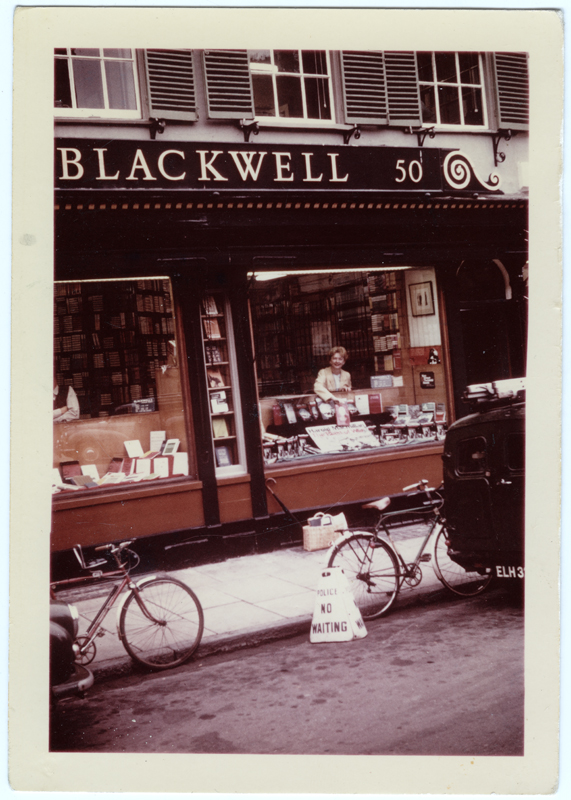 """Image of Clara Thomas leaning over the display window of Blackwell's Book Store in Oxford, England, holding a copy of her book above a display featuring Harold Macmillan's """"The Blast of War"""". Clara is smiling out to the photographer, who is positioned from a distance, probably in the middle of the street, 1967. Clara Thomas Archives & Special Collections, Clara Thomas fonds, F0432, image no. ASC07978."""