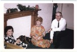 Image of Clara Thomas seated on the floor of a living room beside her husband Morley. An unknown woman is seated at a chair in the left hand side of the frame, December 1967. Clara Thomas Archives & Special Collections, Clara Thomas fonds, F0432, image no. ASC07979.