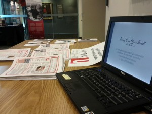 Low angle photograph of laptop, promotional material, on a table at the Archives of Ontario.