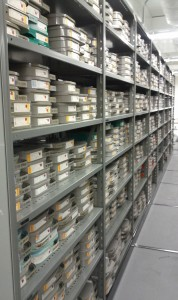 Shelving range containing hundreds of video reels in plastic cases.
