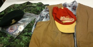 A green military uniform is visible, as is a black military beret and a plastic bag full of badges, pins and medals. Also visible is a flannel checkered shirt, a beige heavy fabric vest and a Calgary Flames baseball cap.