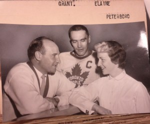 Toronto Maple Leafs coat Billy Reay leans on edge of rink barrier speaking to Elaine Grant, who rests her elbow on the barrier. Captain George Armstrong in his captain's jersey is standing between them..
