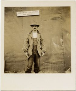 Picture of Arnold Hoffman from ankles up, wearing a hate and jacket, stnading infront of a metal building and sign above him.