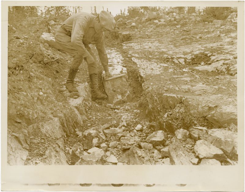 Miner in Canada : Image of man leaning over to work with soil. He is wearing boots and a hate.