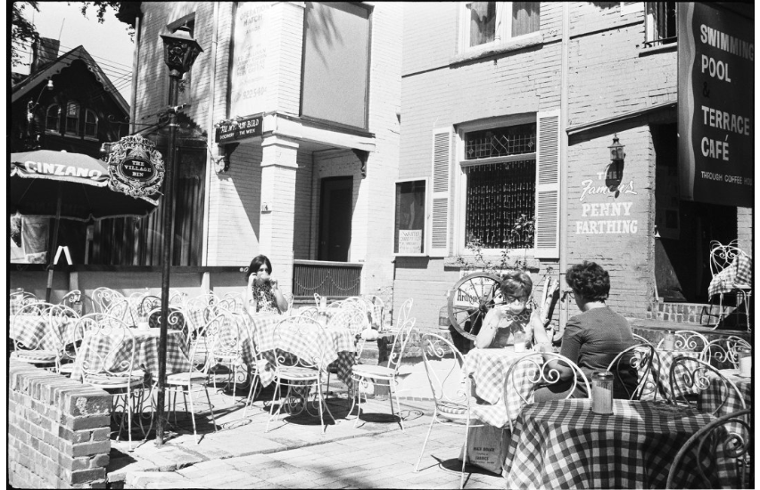 Image of cafe patio. Two individuals sitting at separate tables. Image is of cafe the Penny Farthing which was a popular scene for Yorkville and Toronto's folk music scene.