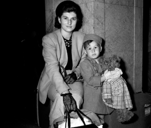 A woman, wearing patterned gloves and holding handles of purse and bag with right hand, sitting on luggage next to child, wearing gloves and pillbox-style hat and holding teddy bear.