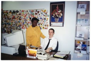 Image of Jean Augustine in yellow suit posing beside young man in white shirt and black tie seated at an office desk. Behind them is a series of wall hangings holding many political and activist buttons.