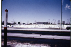 Colored image of Keele Street with a bus stop pole in the foreground and a snowy field with the Ross Humanities building in the very distant background.