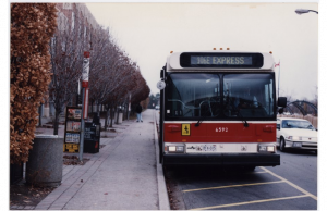 Image of a 106E Express bus standing in front of its stop at the bus loop near York Lanes. Cars driving and a person walking are visible in the background.