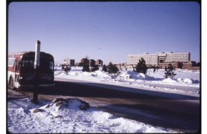 Image of a bus stopping on the road with snow on the ground and the Ross Building in the distance.