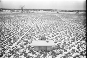 Man sitting at a desk in the middle of an empty field.